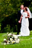 Bridal bouquet on lawn, bride and groom in background