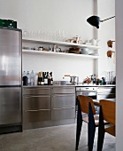 Fifties-style wooden chairs in stainless steel kitchen