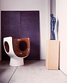 White, plastic shell chair with brown, leather upholstery opposite figure on pedestal