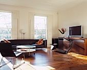 Black leather, retro armchairs and couch in living room with classic ambience