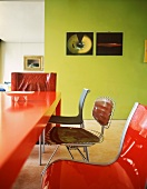 Red, plastic table with chairs in a variety of styles in front of green-painted wall