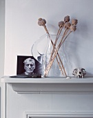 Dried poppy heads in glass jug next to photograph on mantelpiece