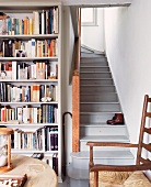 Corner of room with fitted bookcase and old, grey wooden staircase