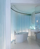 Free-standing bathtub with floor-mounted taps in front of curved, reflective wall
