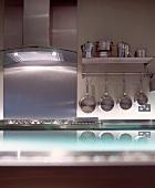 Stainless steel pots hanging beneath kitchen shelf next to extractor hood