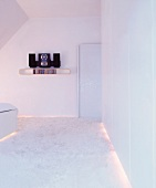White bedroom with flokati carpet and indirect lighting under furniture
