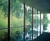 Reflections on surface of swimming pool in building with glass facade