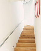 Narrow, modern staircase with wooden stairs
