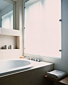 Bathtub in front of frosted glass window