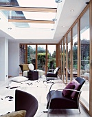 Black, retro armchairs next to glass wall in living space