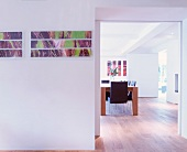 Modern pictures on wall next to wide doorway and view of dining table
