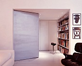 Living space with angled partition and view of bookcase