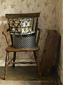 Old suitcase in corner & hatboxes on wooden chair