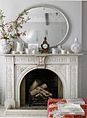 Open fireplace with ornamental surround & mirror above