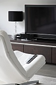 White, swivel chair in front of TV