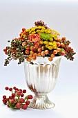 Herbstliches Gesteck mit Blüten & Beeren in silberner Vase