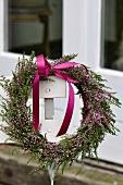 Heather wreath with purple ribbon