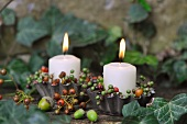Candles in metal tart cases decorated with autumnal berries & acorns