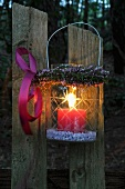 Storm lamp with wreath of heather hanging on wooden fence