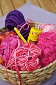 Wool basket with balls of wool, crocheting needle and knitting dolly
