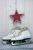 White, children's ice skates and red star against wooden wall