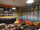 Shell chairs with colourful upholstery and multi-coloured wall panels in retro-style bar
