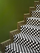 Stair treads with spotted carpet against green wall