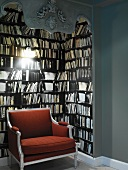 Decorative, dark book alcove with stylish, red upholstered armchair