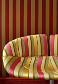 Striped patterns on elegant chair with fabric cover and wallpaper