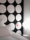Expressive wall design in hotel room with irregular, white circles on black background