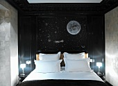Themed hotel room with stylised night sky on wall behind double bed