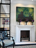 Modern art and bouquets above burning fire in elegant living room