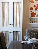 Dining table with crockery in front of elegant fitted cupboard with fabric panels in doors