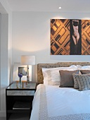 Modern picture above double bed with upholstered headboard - mix of styles and patterns in bedroom