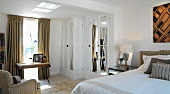 Comfortable bedroom with desk under window and fitted wardrobe with mirrored doors
