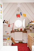 White cabin bedroom for two children with colourful decorations in steeply slanting ceiling structure