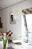 Paper star lightshade and old, white-painted metal rocking chair in front of slanting panoramic window