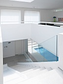 Staircase leading down from open-plan living room with view of sunny indoor swimming pool