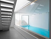 Glass wall in stairwell with view of narrow indoor swimming pool