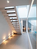 Bottom view of staircase lit by wall spotlights next to glass wall leading to indoor swimming pool