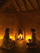 Meditative atmosphere in simple clay building with organic lines - two women sitting on floor cushions in front of blazing fire in fireplace