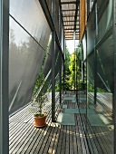 Sunshade panels offset from glass facade above wooden decking