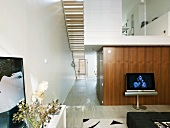 Double-height living room, view of stairs from below and glazed gallery level in modern house with narrow floor plan