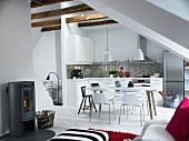 Open-plan attic room in youthful Scandinavian style with simple kitchen, dining area and wood burner