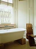 Free-standing modern bathtub supported on wooden blocks and organic, gnarled wood chair