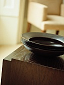 Dark, exotic bowls on traditional wooden cabinet