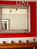 'Love' mirror with silver wooden frame on red wall with reflection of male nude