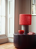 Lamp with red shade and red ornaments on modern table next to terrace door and white wall panel