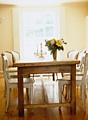 Rustic dining table in natural wood with a mixture of chair styles and bouquet