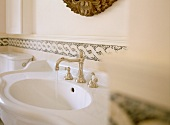 Curved sink with silver, antique-style tap fittings against wall with plaited border
